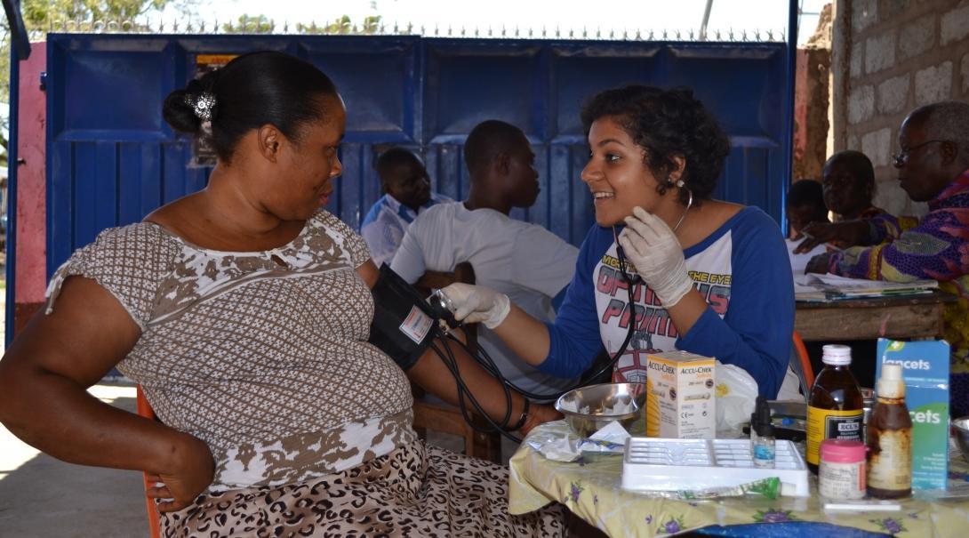 Durante sus Prácticas de Matronería en Ghana, una voluntaria ayuda con chequeos médicos.